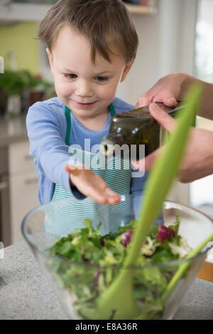Garçon d'aider dans la préparation de la mère de la salade, Close up