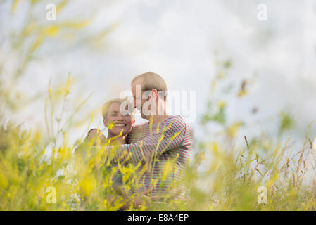 Young couple relaxing in field Banque D'Images