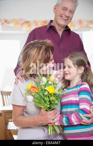Petite-fille à sa grand-mère bouquet remise et grand-père en arrière-plan Banque D'Images