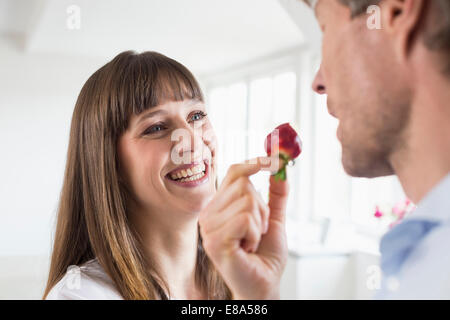 Mid adult Woman feeding strawberry pour homme mûr, smiling Banque D'Images