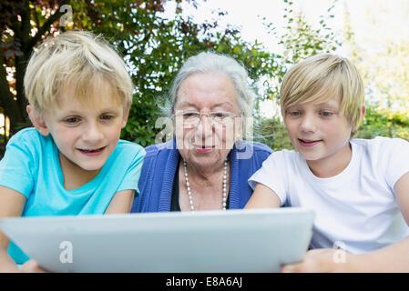 Grand-mère et ses deux petits-fils à la tablette à l'ordinateur Banque D'Images