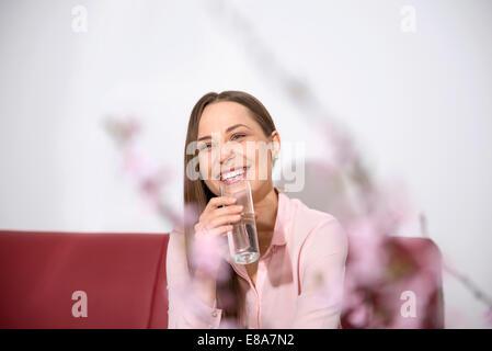 Jeune femme canapé sitting smiling l'eau potable Banque D'Images