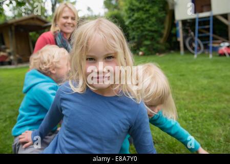 Mère jouant avec trois jeunes enfants dans jardin Banque D'Images