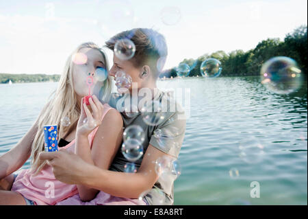 Couple soufflant des bulles de savon sur une jetée au lac Banque D'Images