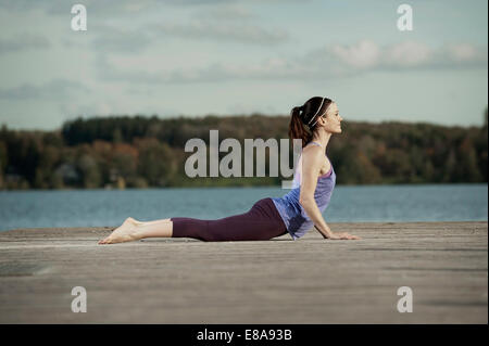 Woman practicing yoga on Jetty, Woerthsee, Bavière, Allemagne