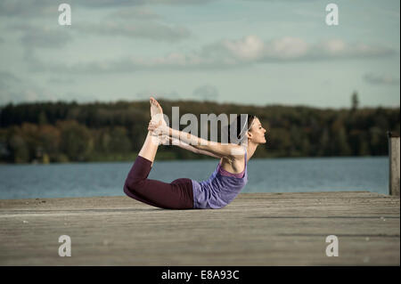 Woman practicing yoga on Jetty, Woerthsee, Bavière, Allemagne Banque D'Images