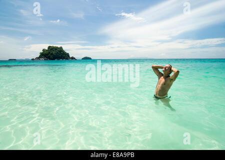Homme debout, dans l'océan, Koh Lipe, Thaïlande Banque D'Images