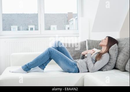 Jeune femme avec livre ouvert posé sur table à la maison Banque D'Images