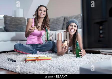 Deux amies côte à côte sur un tapis à la maison à regarder la télévision