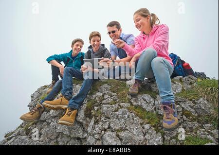 Père enfants adolescents assis sur des rochers à l'aide d'iPad Banque D'Images
