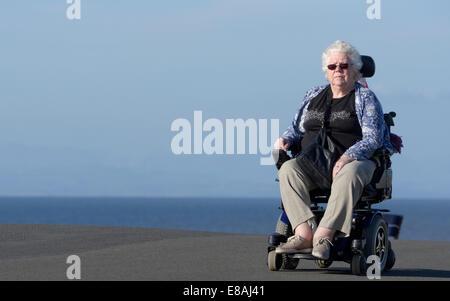 Vieille dame en fauteuil roulant sur un sentier côtier à Blackpool, lancashire, uk Banque D'Images