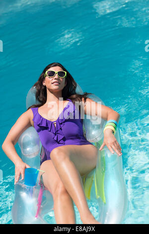 Jeune femme en train de bronzer sur la lit dans la piscine Banque D'Images