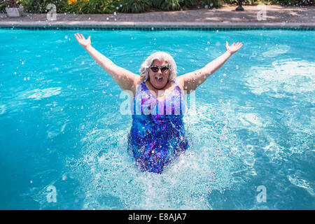 Portrait of mature woman splashing about in swimming pool Banque D'Images