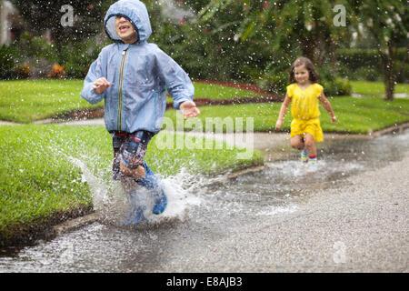 Garçon et sœur de porter des bottes en caoutchouc en marche et de s'éclabousser dans la flaque de pluie Banque D'Images