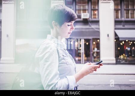 Femme à l'aide du smartphone sur le street, New York, États-Unis