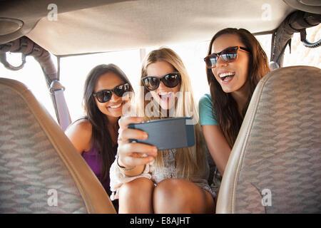 Trois jeunes femmes prenant sur smartphone selfies in back seat of car Banque D'Images