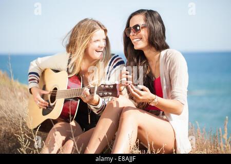 Deux jeunes femmes avec la guitare acoustique à l'autre, Malibu, California, USA Banque D'Images