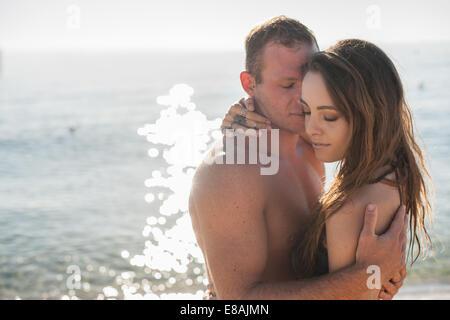 Young couple embracing on beach, Castiadas, Sardaigne, Italie Banque D'Images