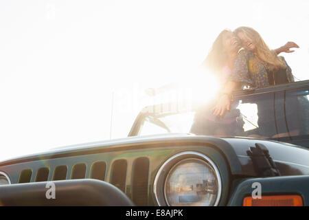 Deux jeunes femmes debout en arrière de jeep Banque D'Images