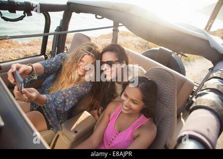 Trois jeunes femmes prenant sur smartphone selfies en jeep à côte, Malibu, California, USA Banque D'Images