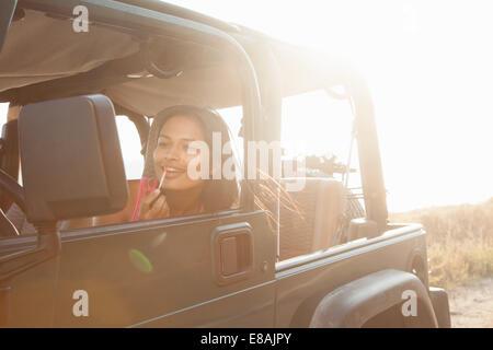 Jeune femme en jeep à l'autre application de lustre de lèvre, Malibu, California, USA Banque D'Images