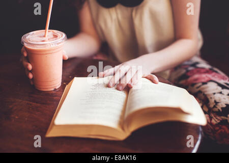 Woman Reading book on table Banque D'Images