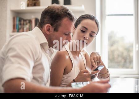 Jeune couple looking at smartphone à table de cuisine Banque D'Images