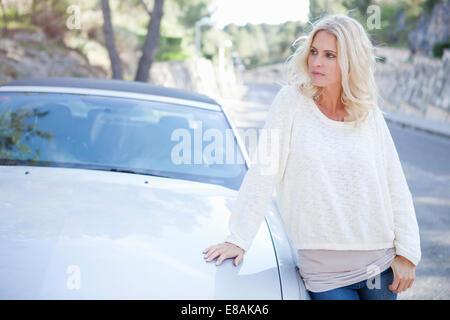 Femme à côté de sa voiture décapotable Banque D'Images