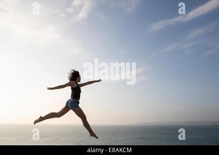 Femme sautant contre skyline Banque D'Images
