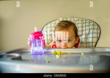 Portrait de petite fille timide dans une chaise haute Banque D'Images
