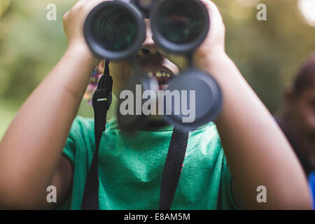 Close up of girl looking through binoculars dans eco camp forestier Banque D'Images