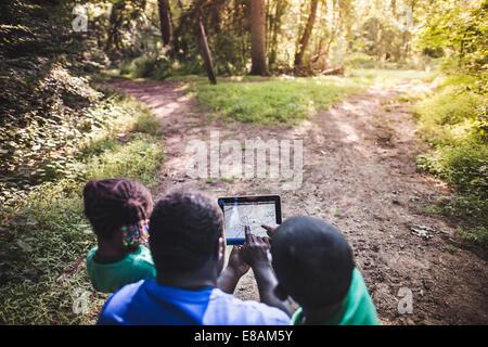Le père avec la fille et le fils de la navigation avec digital tablet in eco camp forestier Banque D'Images