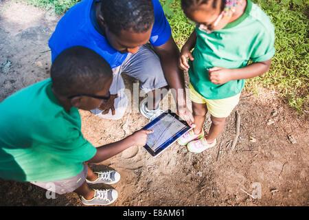 Le père avec la fille et le fils de la navigation avec tablette numérique eco camp à Banque D'Images