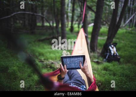 Randonneur couché dans un hamac en forêt à la recherche à la carte on digital tablet Banque D'Images