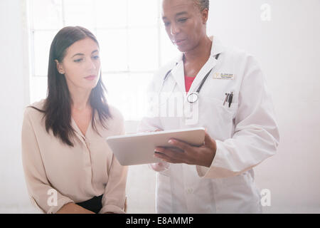 Doctor using digital tablet en consultation Banque D'Images