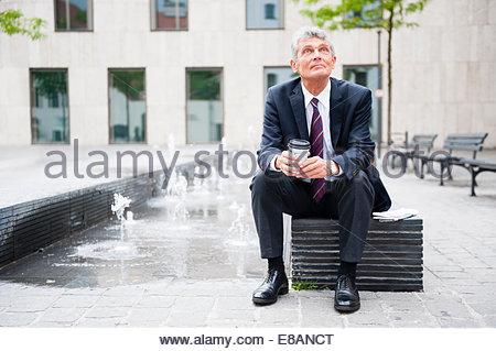 Senior businessman sitting in city plaza café à emporter Banque D'Images