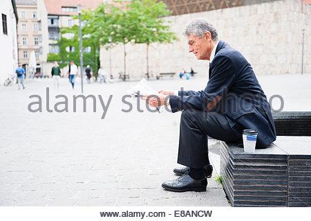 Senior businessman sitting in city plaza reading newspaper Banque D'Images