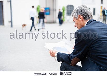 Senior businessman sitting in city plaza journal grand format de lecture Banque D'Images