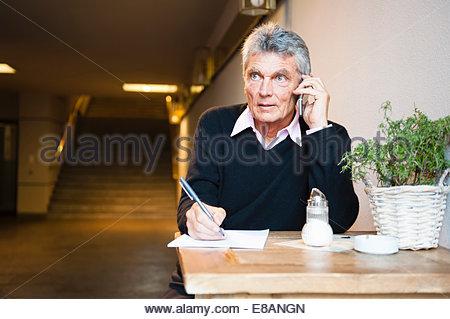 Senior businessman making notes tout en bavardant sur smartphone in cafe Banque D'Images