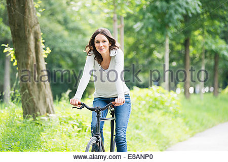 Portrait of mid adult woman sitting in park Banque D'Images