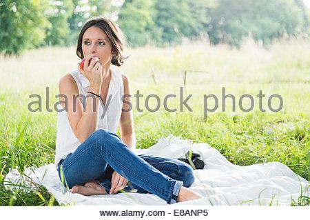Mid adult woman sitting on picnic blanket dans la zone de manger une pomme Banque D'Images