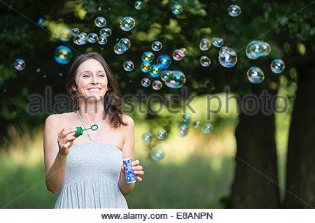 Mid adult woman blowing bubbles à woodland Banque D'Images