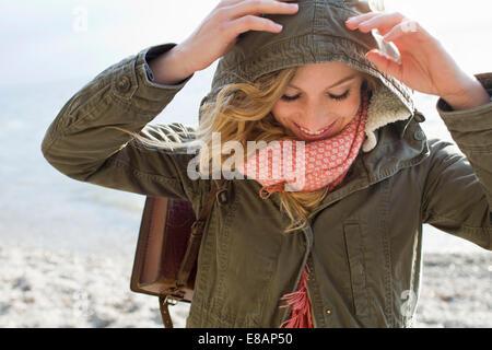 Femme tout enveloppé sur plage de vent Banque D'Images