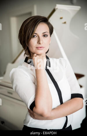 Young woman resting chin on hand, portrait Banque D'Images