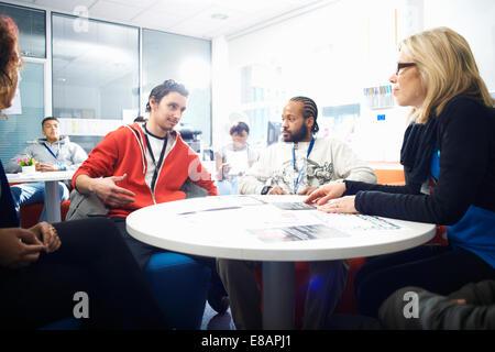 Professeur de sexe féminin et un groupe d'étudiants d'avoir une discussion informelle dans la salle de classe Banque D'Images