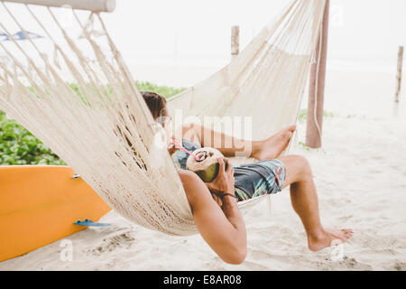 L'eau de coco Man enjoying in hammock on beach Banque D'Images