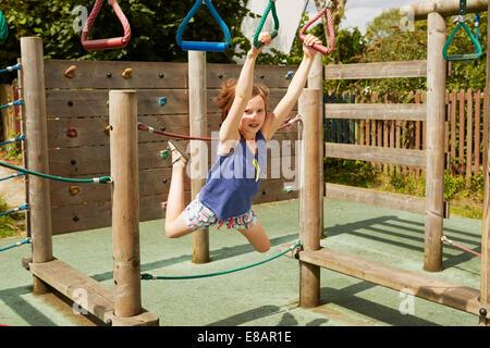 Fille énergique jouant sur des balançoires en aire de jeux Banque D'Images