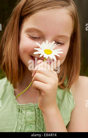Portrait of Girl in garden holding up daisy Banque D'Images