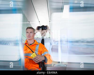 Le capitaine du navire et travailleur à l'aide de jumelles sur le pont du navire avec des réflexions sur la fenêtre Banque D'Images