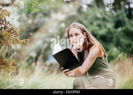 Jeune femme avec lecture de livre dans le champ Banque D'Images